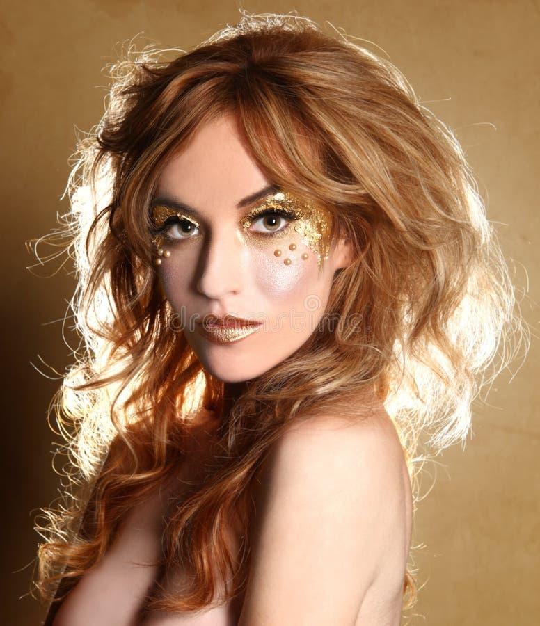 Mujer hermosa adornada con los cosméticos de la hoja de oro foto de archivo libre de regalías