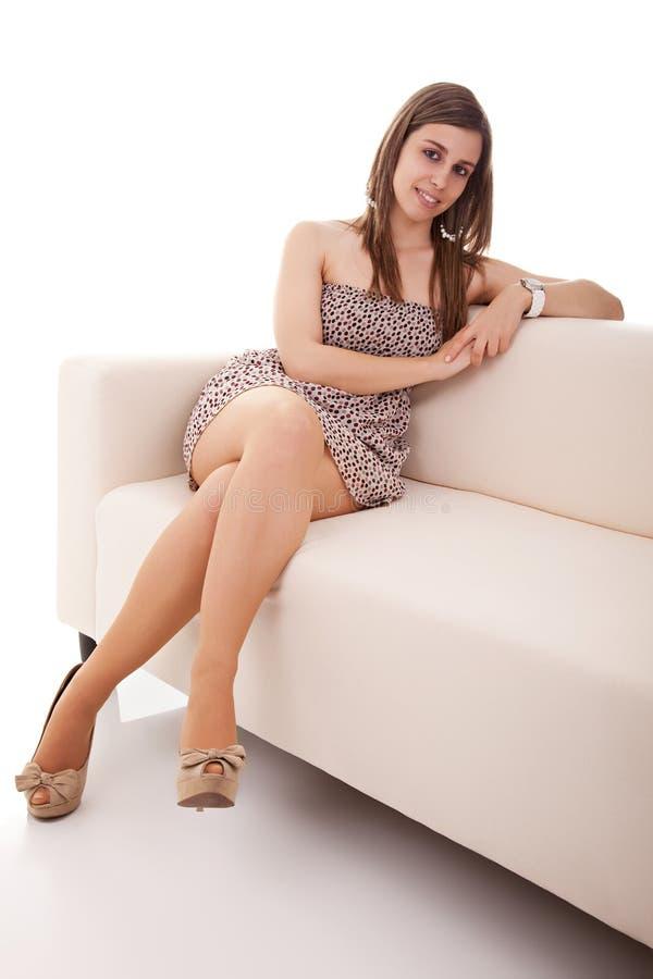 Mujer hermosa asentada en un sofá blanco fotos de archivo