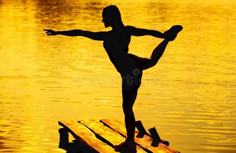 Mujer hermosa, atlética que hace yoga en el puente viejo, de madera foto de archivo libre de regalías