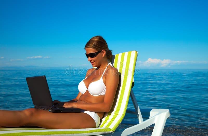 Mujer hermosa atractiva en bikiní usando la computadora portátil imagen de archivo