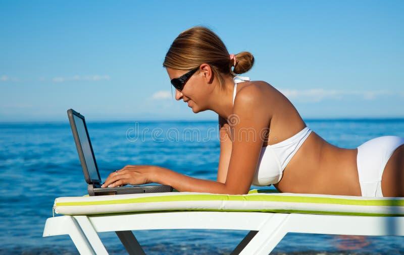 Mujer hermosa atractiva en bikiní usando la computadora portátil imagen de archivo libre de regalías