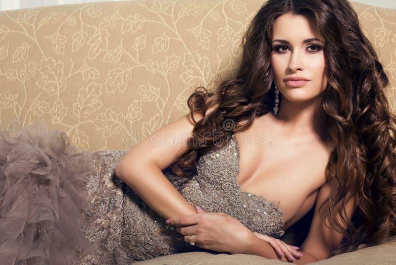 Mujer hermosa atractiva en el vestido lujoso que miente en el diván fotos de archivo libres de regalías