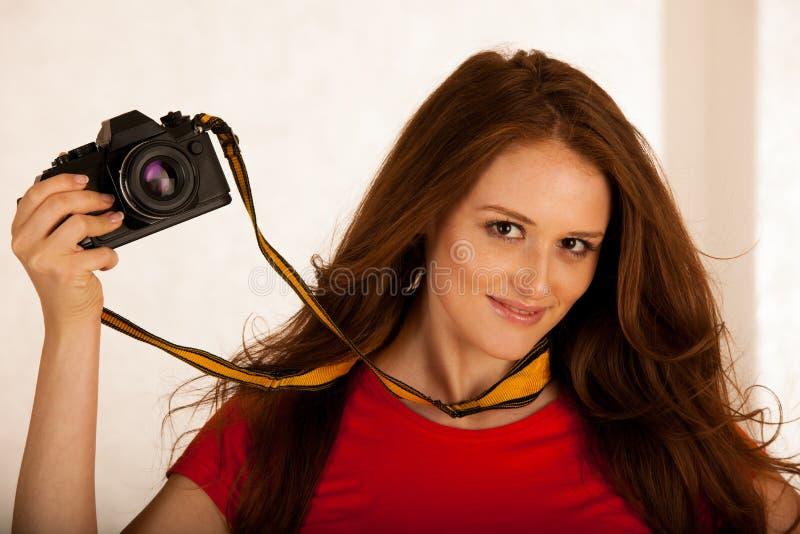 Mujer hermosa atractiva que sostiene una cámara retra foto de archivo libre de regalías