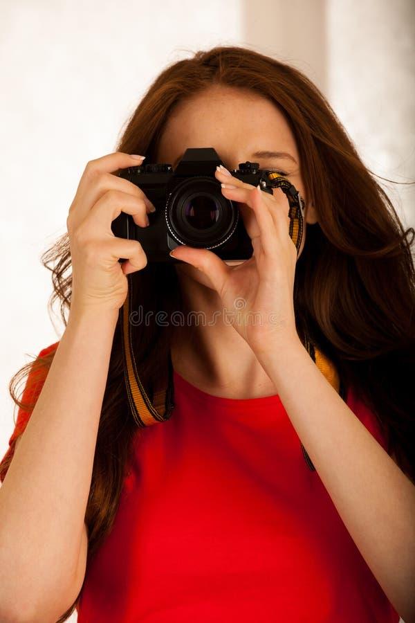 Mujer hermosa atractiva que sostiene una cámara retra fotografía de archivo libre de regalías