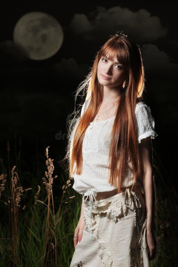 Mujer hermosa bajo la luna foto de archivo libre de regalías