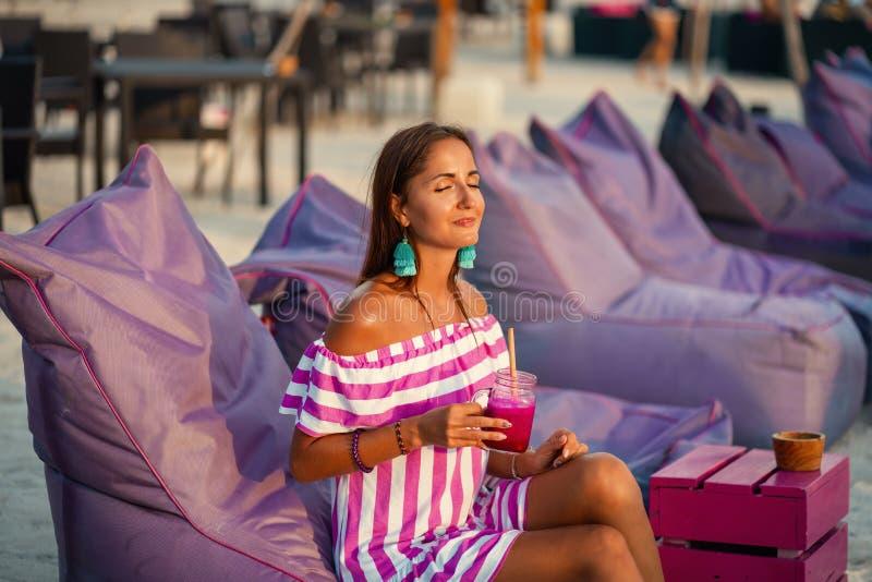 Mujer hermosa bronceada que descansa sobre los sof?s de la playa y que bebe un c?ctel La muchacha sonr?e y goza del sol El balnea imagenes de archivo