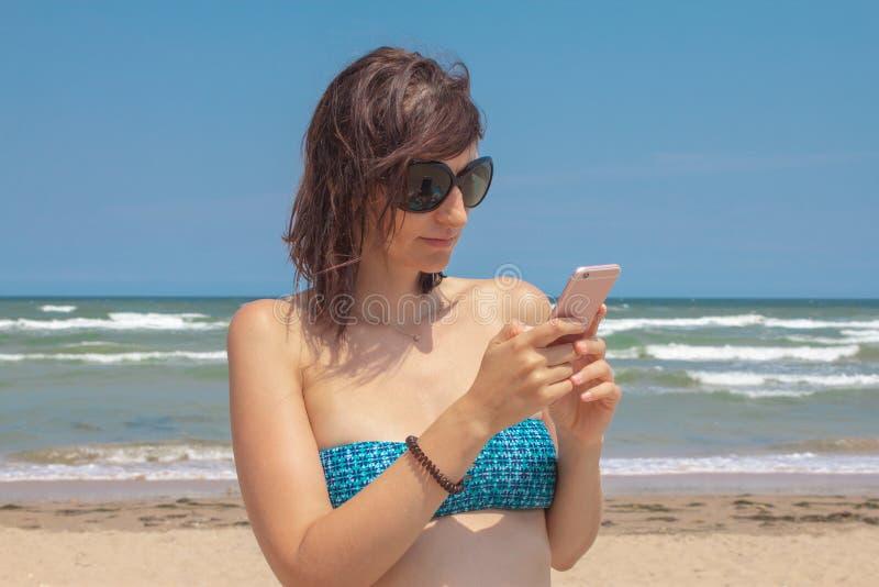 Mujer hermosa caucásica atractiva en el bikini que manda un SMS en el fondo del mar en la playa imágenes de archivo libres de regalías