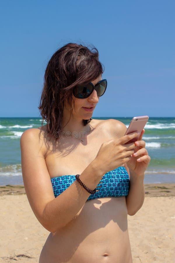 Mujer hermosa caucásica atractiva en el bikini que manda un SMS en el fondo del mar en la playa imagenes de archivo