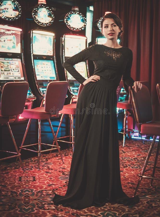 Mujer hermosa cerca de las máquinas de ranuras en un interior de lujo del casino fotos de archivo libres de regalías