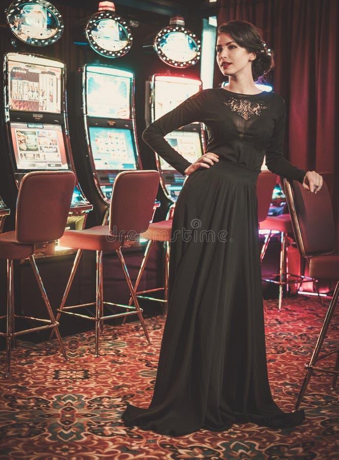 Mujer hermosa cerca de las máquinas de ranuras en un interior de lujo del casino foto de archivo