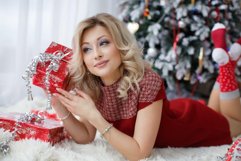 Mujer hermosa cerca de un árbol de navidad con una taza de café con las melcochas imagen de archivo