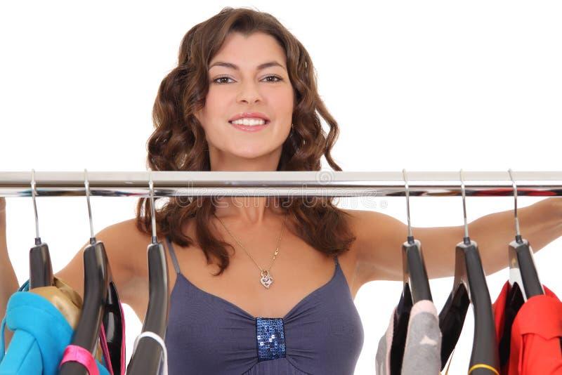 Mujer hermosa cerca del estante con las suspensiones foto de archivo libre de regalías