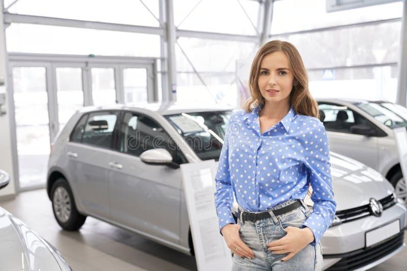 Mujer hermosa, cliente de la concesión de coche que presenta en la sala de exposición imagenes de archivo