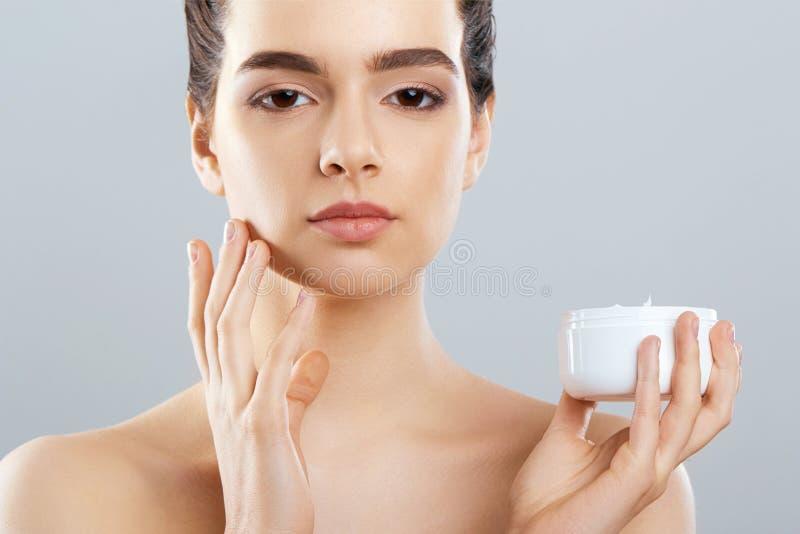 Mujer hermosa con crema de cara Protección de piel Cuidado de piel Spa Una hembra joven sostiene la crema hidratante fotos de archivo libres de regalías