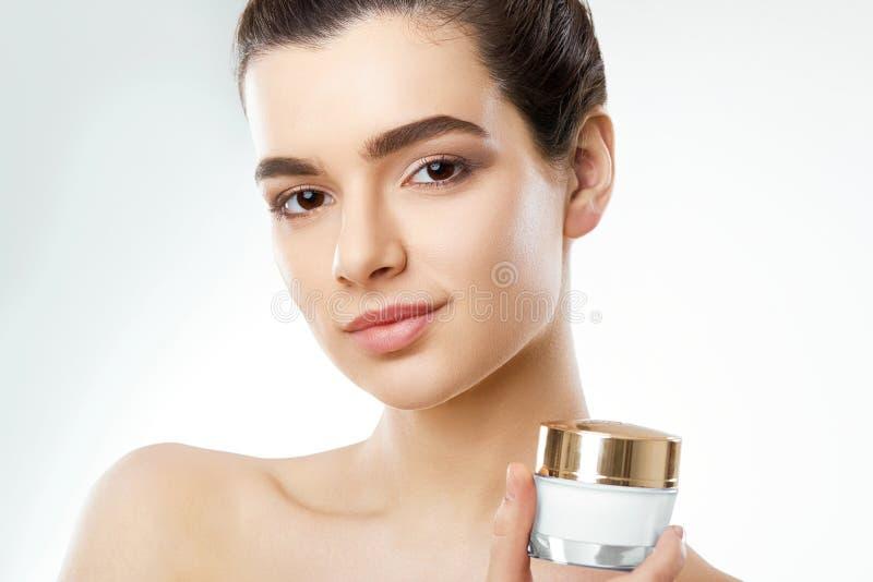 Mujer hermosa con crema de cara Protección de piel Skincare Spa Una hembra joven celebra la crema hidratante y la sonrisa imágenes de archivo libres de regalías