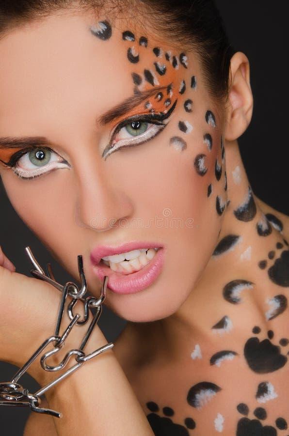 Mujer hermosa con el arte animal y la pulsera de la cara imagen de archivo libre de regalías