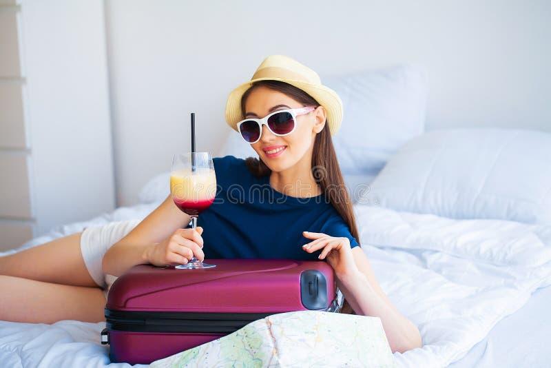 Mujer hermosa con el cóctel y la maleta en cama en sitio del hootel imagen de archivo libre de regalías