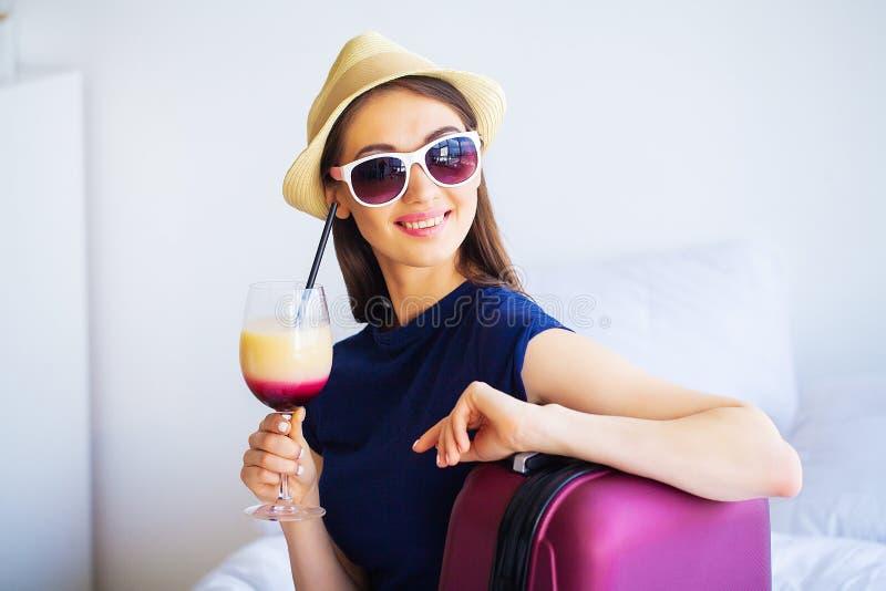 Mujer hermosa con el cóctel y la maleta en cama en sitio del hootel imagenes de archivo