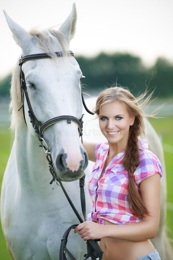 Mujer hermosa con el caballo gris imagenes de archivo