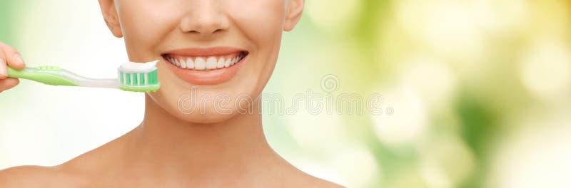 Mujer hermosa con el cepillo de dientes foto de archivo