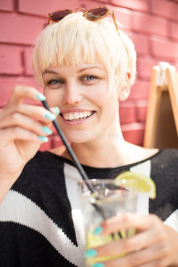 Mujer hermosa con el coctel en café foto de archivo libre de regalías
