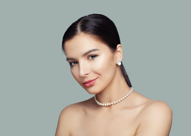 Mujer hermosa con el collar blanco de la joyería de las perlas de la piel que lleva sana foto de archivo