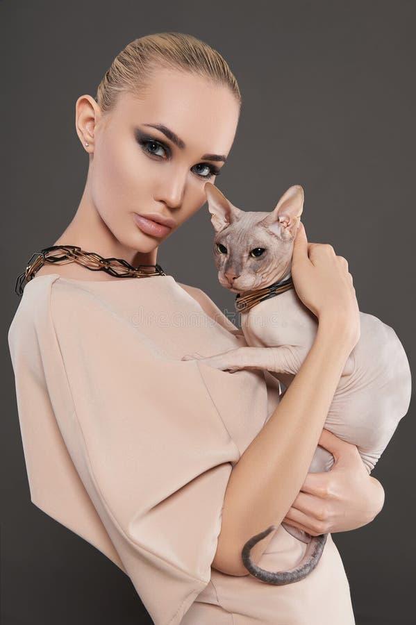 Mujer hermosa con el gato de Sphynx fotos de archivo libres de regalías