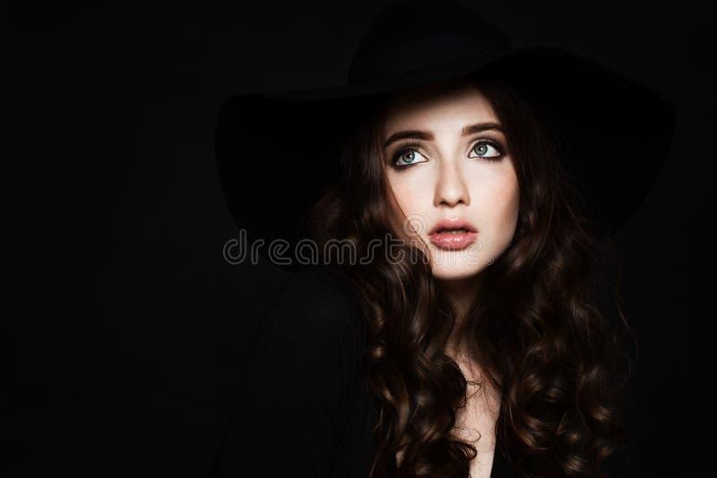 Mujer hermosa con el maquillaje y el pelo rizado que miran para arriba imagen de archivo