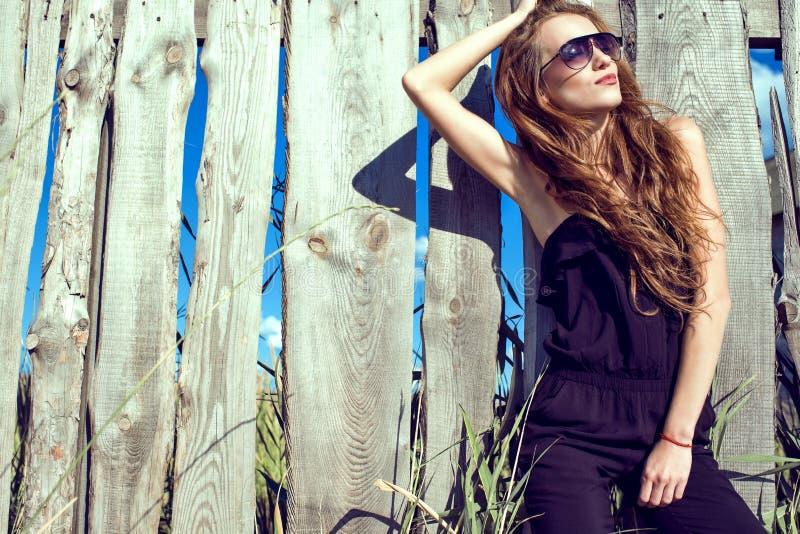 Mujer hermosa con el mono que lleva del pelo largo de la castaña y las gafas de sol tipo aviador de moda en la cerca de madera fotos de archivo libres de regalías