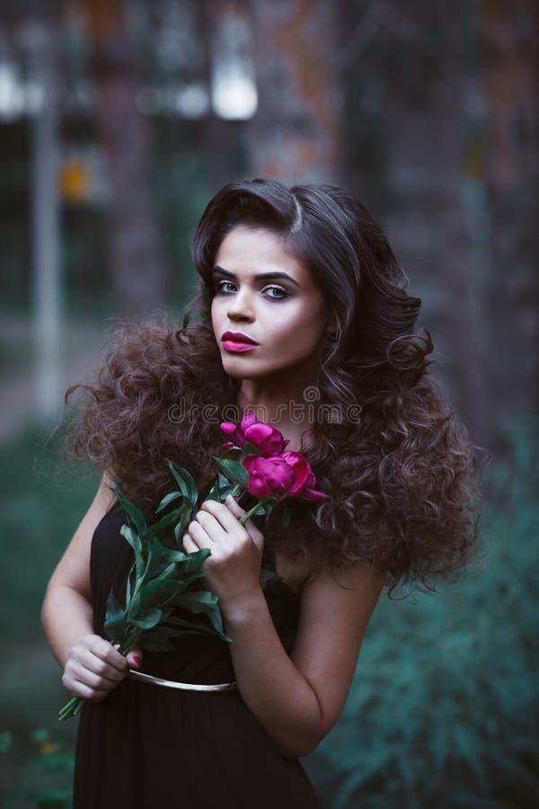 Mujer hermosa con el peinado creativo que sostiene peonías púrpuras foto de archivo libre de regalías