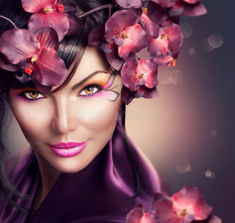 Mujer hermosa con el peinado de la flor de la orquídea imagen de archivo