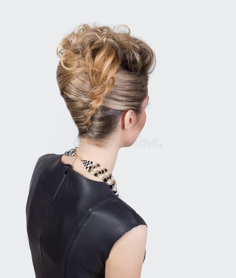 Mujer hermosa con el peinado del salón de la tarde Peinado complicado para el partido fotografía de archivo