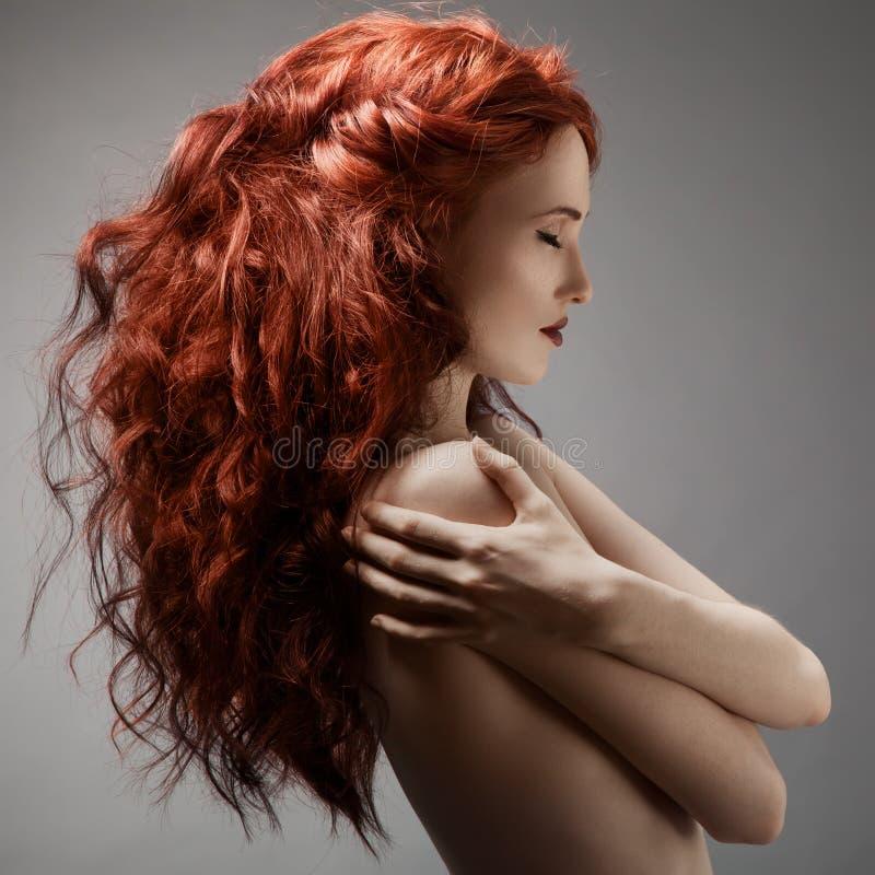 Mujer hermosa con el peinado rizado contra fondo gris imágenes de archivo libres de regalías