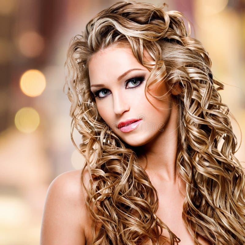 Mujer hermosa con el peinado rizado largo imagenes de archivo