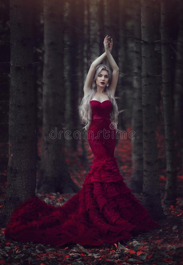Mujer hermosa con el pelo blanco largo que presenta en un vestido rojo lujoso con un tren largo que se coloca en un bosque del pi fotografía de archivo
