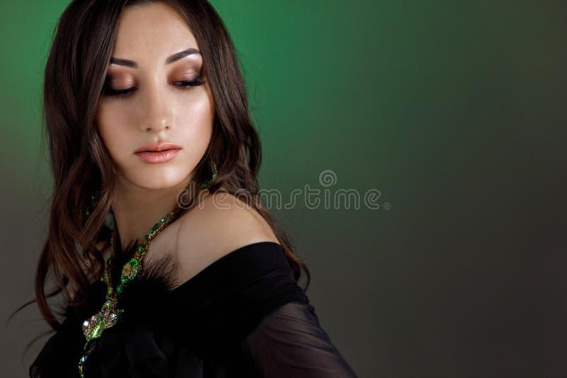 Mujer hermosa con el pelo hermoso, maquillaje y con el collar de lujo en fondo verde oscuro fotos de archivo libres de regalías
