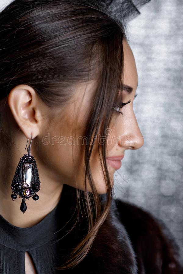 Mujer hermosa con el pelo hermoso, maquillaje y con los pendientes de lujo imagen de archivo