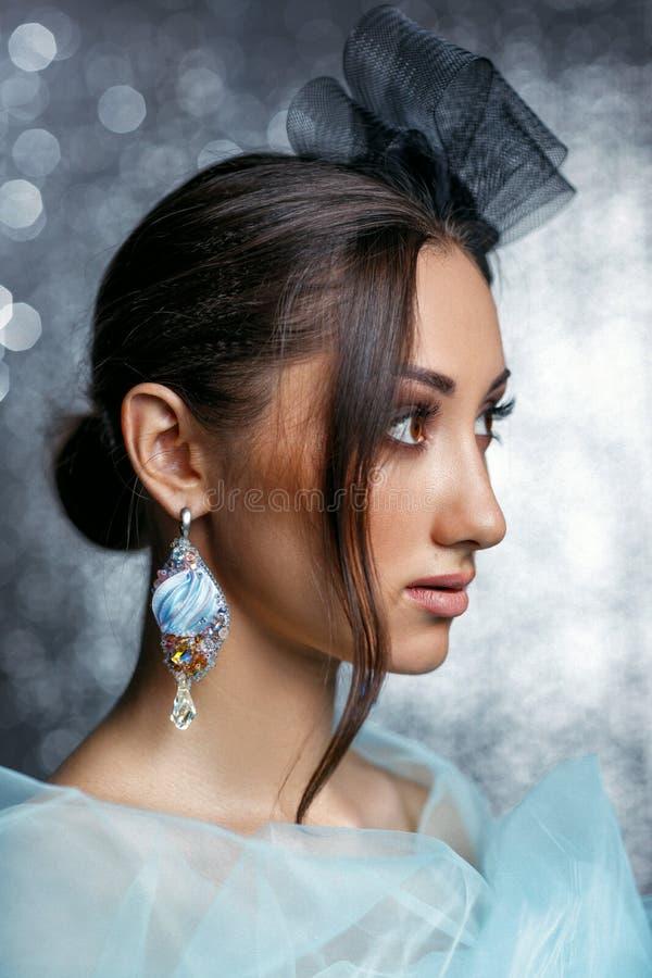 Mujer hermosa con el pelo hermoso, maquillaje y con los pendientes de lujo imagen de archivo libre de regalías
