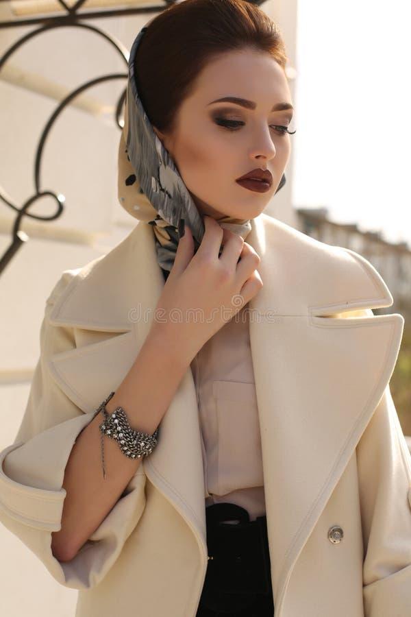 Mujer hermosa con el pelo oscuro en bufanda elegante de la capa y de la seda fotografía de archivo