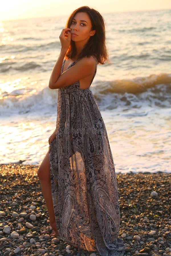 Mujer hermosa con el pelo oscuro en el vestido elegante que presenta en la playa de la puesta del sol imagen de archivo libre de regalías