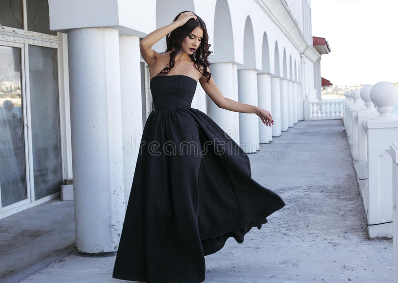 Mujer hermosa con el pelo oscuro en vestido negro elegante fotos de archivo libres de regalías