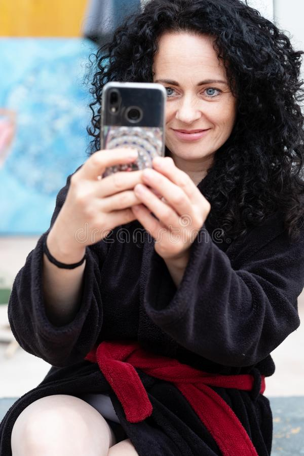 Mujer hermosa con el pelo rizado oscuro en la sonrisa de fotografía de la albornoz con el smartphone foto de archivo libre de regalías