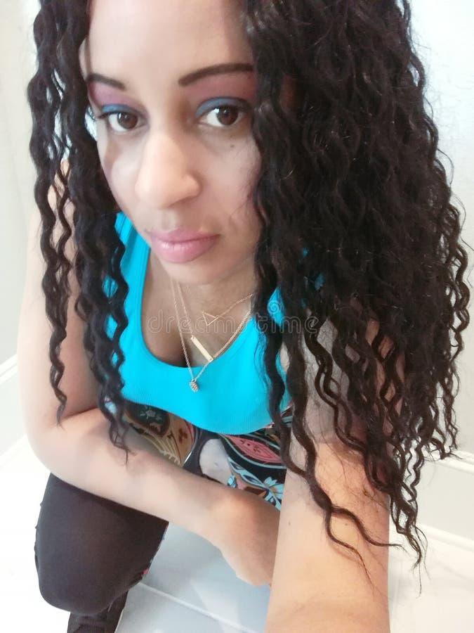 Mujer hermosa con el pelo rizado que ejercita en un top azul imagen de archivo libre de regalías
