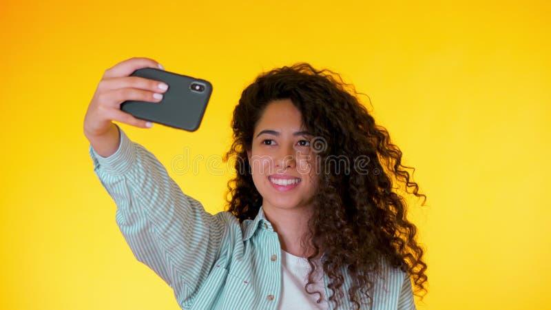 Mujer hermosa con el pelo rizado que sostiene y que usa el tel?fono elegante para filmarse en estudio amarillo Femenino usando te fotografía de archivo