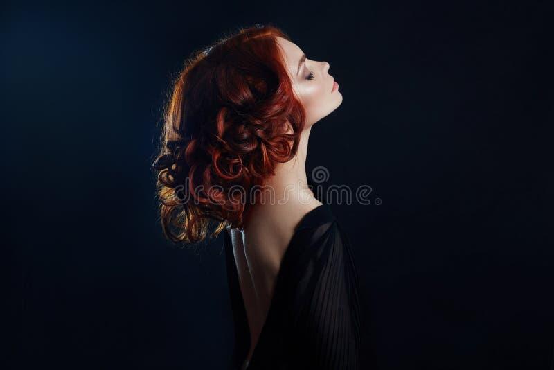 Mujer hermosa con el pelo rojo en un fondo negro Retrato de una mujer acertada, piel pura, maquillaje natural, cara del cuidado d imagen de archivo