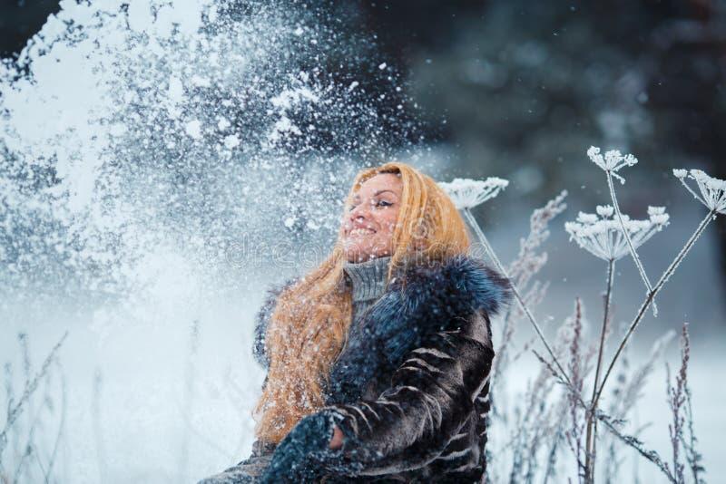 Mujer hermosa con el pelo rojo largo en una nieve que lanza nevosa de la pastinaca de vaca encima del foco selectivo imagen de archivo