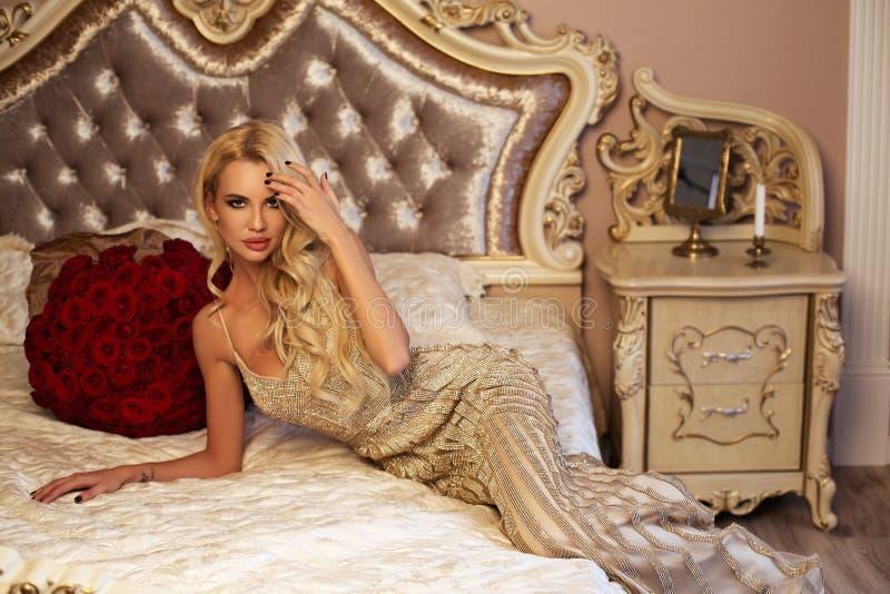 Mujer hermosa con el pelo rubio en la ropa lujosa que presenta con imágenes de archivo libres de regalías