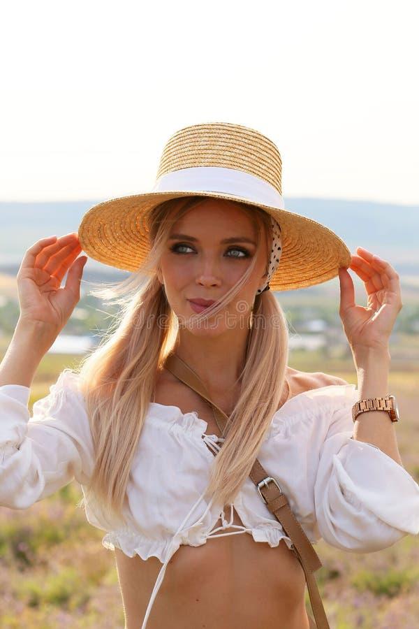 Mujer hermosa con el pelo rubio en ropa elegante y accesorios que presentan en campo de florecimiento de la lavanda fotografía de archivo libre de regalías