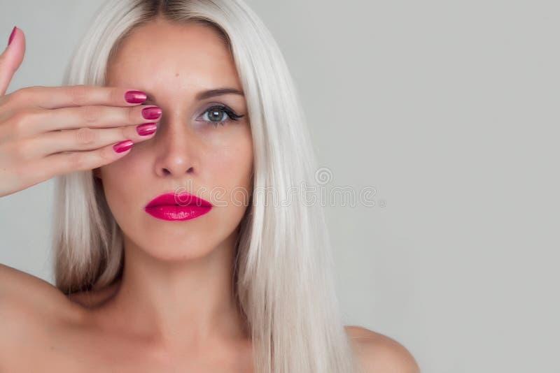 Mujer hermosa con el pelo rubio Modelo de moda con el lápiz labial rojo y los clavos rojos imagenes de archivo
