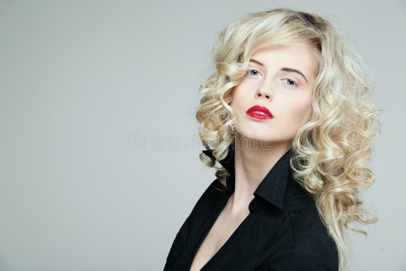 Mujer hermosa con el pelo rubio rizado largo. fotos de archivo